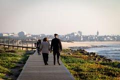 Höga par går på strandpromenad fotografering för bildbyråer