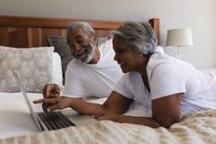 Höga par genom att använda bärbara datorn i sovrum hemma royaltyfri foto