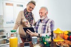Höga par genom att använda den digitala minnestavlan i köket Arkivbilder