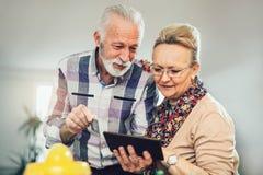 Höga par genom att använda den digitala minnestavlan i köket Arkivfoto