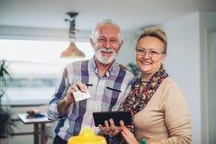 Höga par genom att använda den digitala minnestavlan i köket Royaltyfria Foton