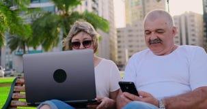 Höga par genom att använda en bärbar dator, medan sitta på stol i, parkerar lager videofilmer