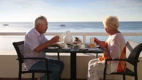 Höga par har frukosten på det utomhus- hotellet stock video