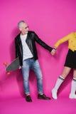 Höga par i läderomslag som poserar med skateboard- och innehavhänder som isoleras på rosa färger royaltyfri bild