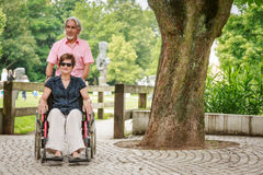 Höga par i rullstolen som tycker om en dag i parkera Arkivfoto