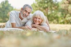 Höga par lägger lyckligt på grasna arkivbild