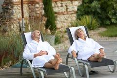 Höga par med badrocken som kopplar av på det wood däcket Royaltyfri Bild