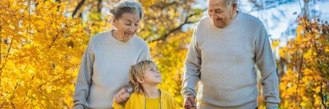 Höga par med behandla som ett barn sonsonen i hösten parkerar Gammelmormor-, gammelfarfar- och stor-sonson BANER royaltyfri bild