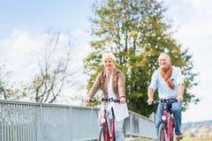 Höga par med cyklar på bron Arkivbilder