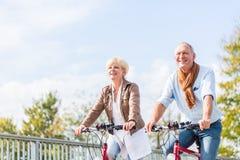 Höga par med cyklar på bron Fotografering för Bildbyråer