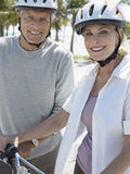 Höga par med cyklar på den tropiska stranden Royaltyfri Foto
