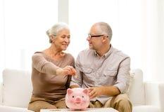 Höga par med pengar och spargrisen hemma Fotografering för Bildbyråer
