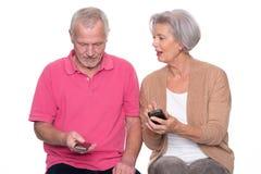 Höga par med smartphonen Arkivfoton