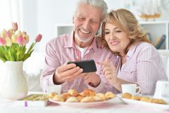 Höga par med smartphonen som dricker te royaltyfria bilder