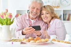 Höga par med smartphonen som dricker te arkivbilder