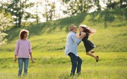 Höga par med sondottern utanför i vårnatur och att ha gyckel fotografering för bildbyråer