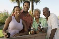 Höga par och mitt--vuxna människan kopplar ihop den hållande camcorderståenden för den höga kvinnan. Arkivfoton