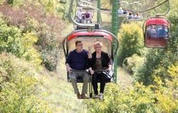 Höga par på en stolelevator som tycker om landskap Royaltyfria Foton