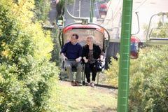 Höga par på en stolelevator som tycker om landskap Royaltyfri Foto