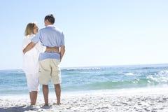 Höga par på ferie som promenerar det Sandy Beach Looking Out To havet Royaltyfri Bild