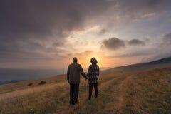 Höga par rymmer händer på kullen på den idylliska solnedgången arkivbild