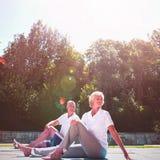 Höga par som övar på poolsiden mot himmel Arkivbilder
