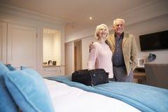 Höga par som ankommer i hotellrum på semester arkivfoto