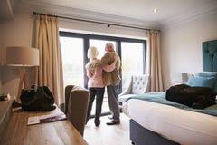 Höga par som ankommer i hotellrum på semester Fotografering för Bildbyråer