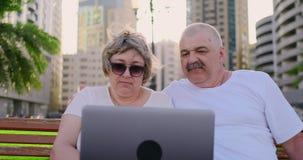 Höga par som använder en bärbar dator i, parkerar på en solig dag arkivfilmer
