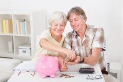 Höga par som beräknar mynt Arkivbild