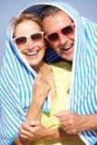 Höga par som beskyddar från Sun på strandferie Arkivfoton