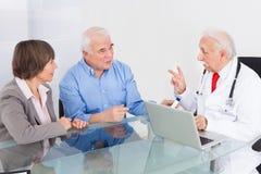 Höga par som diskuterar med doktorn Royaltyfria Bilder