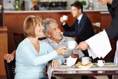 Höga par som dricker kaffe på coffee shop Arkivbilder