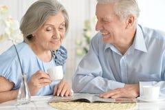 Höga par som dricker te och den läs- tidskriften Arkivbilder