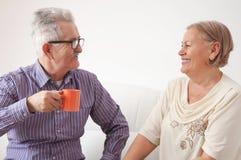 Höga par som dricker te och pratar lyckligt fotografering för bildbyråer