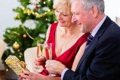 Höga par som firar jul med champagne Arkivfoton