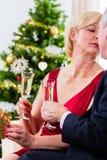 Höga par som firar jul med vin och kyssen Royaltyfri Fotografi