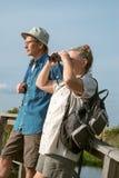 Höga par som fotvandrar och Birdwatching med Binocul arkivfoto