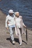 Höga par som går på flodkust på dagen Royaltyfria Foton