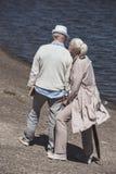 Höga par som går på flodkust på dagen Arkivfoto
