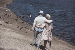 Höga par som går på flodkust på dagen Arkivbilder