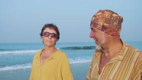 Höga par som går på stranden och talar, steadicamskott lager videofilmer