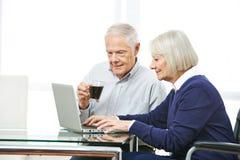 Höga par som gör online-shopping i internet royaltyfria foton