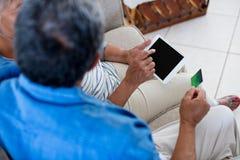 Höga par som gör online-shopping på den digitala minnestavlan Royaltyfri Foto