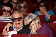 Höga par som håller ögonen på filmen 3D i bio Royaltyfri Bild