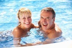 Höga par som har gyckel i simbassäng Fotografering för Bildbyråer