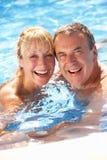 Höga par som har gyckel i simbassäng royaltyfri bild
