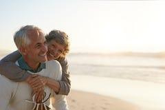 Höga par som har gyckel på stranden royaltyfria foton