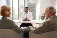 Höga par som har konsultation med manlig doktor In Hospital Office arkivfoton