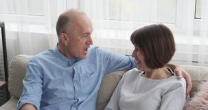 Höga par som har rolig diskussion på soffan lager videofilmer